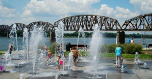 Children play among the water fountain feature with the scenic bridge view overlooking the riverfront.