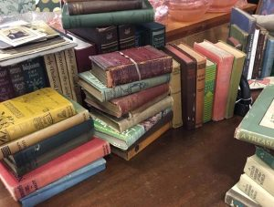 A table of multi-colored antique books at the Elm Consignment and Antique Store