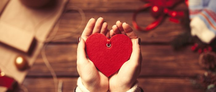 Woman holding a heart shape toy in the hands before wrapping