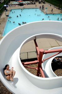 A young girl slides down the white half pipe water slide that overlooks patrons swimming in the L-shaped pool at Atkinson Pool
