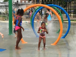 Excited children playing in the water among the Spray Ground play fountains