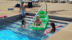A small group of children splash in the water among their inflatable pool toys at Aqua City
