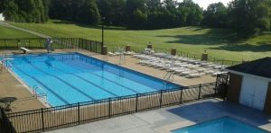 The Country Club pool facility features a shallow/deep swimming pol with diving board and reclining chairs and a smaller wading pool for young children
