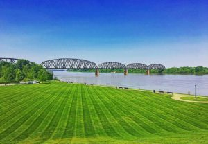 A manicured lawn at Red Banks parks overlooking blue skies and the railroad bridge on the Ohio River.