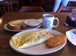 A plated omelette and hash-brown with a side of Texas toast and gravy and a cup of North South coffee