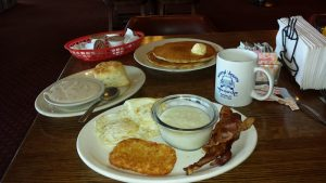 A hearty truck stop breakfast with a double stack of buttery pancakes, biscuits and gravy, eggs over easy, grits, bacon and a hash-brown accompanied by a cup of North South coffee
