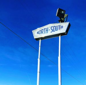Vintage North South signage against a blue winter sky