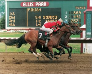 A tight finish between three thoroughbred horses racing at Ellis Park
