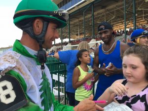 A jockey signs an autograph for a little girl in the crowd at Ellis Park
