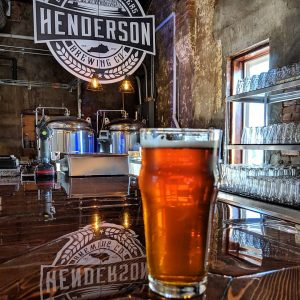 An amber pint of cold craft beer sits at the bar at Henderson Brewing Company