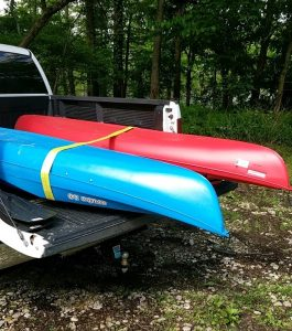 A red & blue kayak in the back of a white pick-up truck at the Henderson Sloughs.