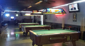 Algonquin's bar with three pool tables and unique overhead lighting