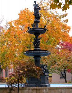 The Central Park fountain with bright orange fall foliage in the background.