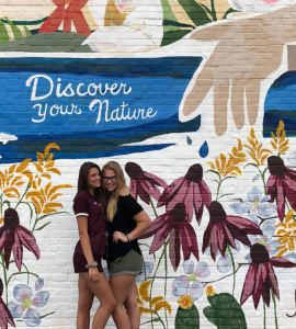 Two visitors hug and pose in front of a colorful two story mural at The Perch.